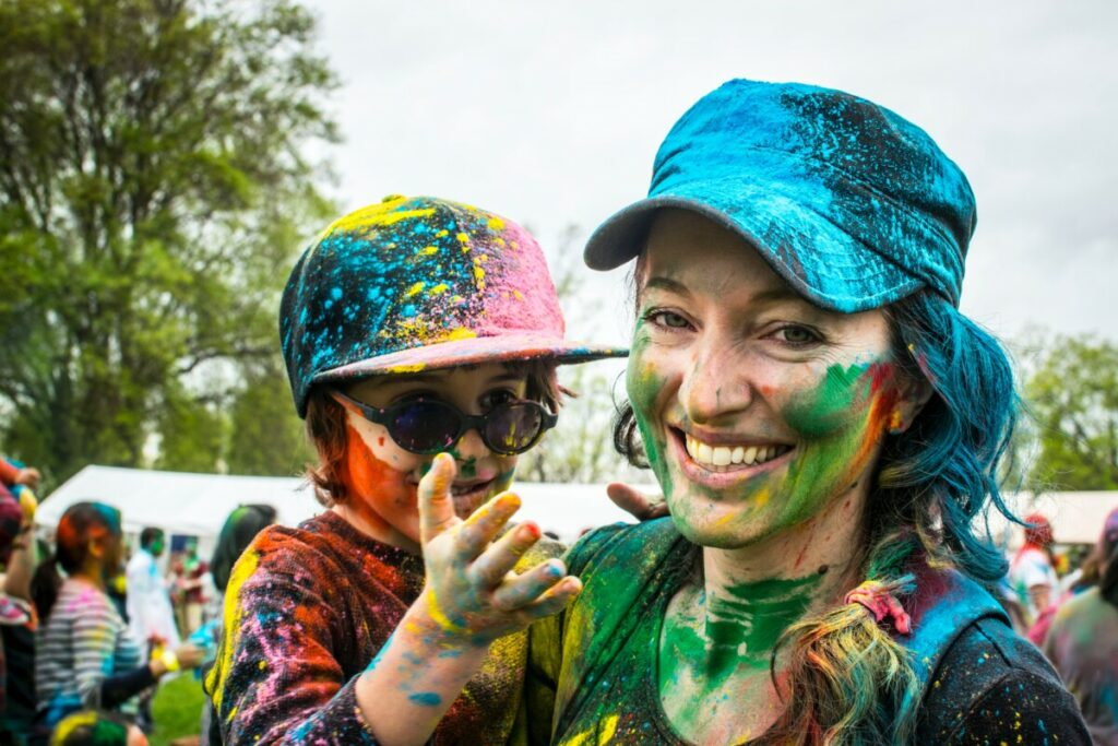 woman carrying child on color run