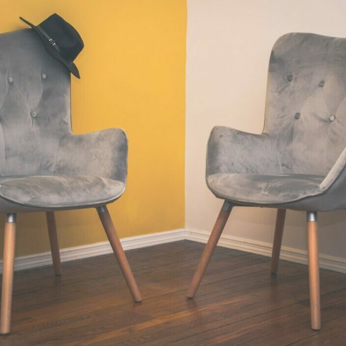 gray padded chair on brown wooden floor